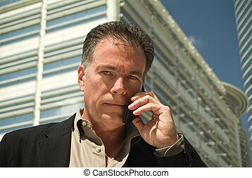 Conducting Business - A man on a cell phone with high rise...