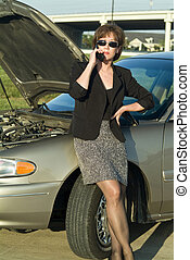 Brokendown - A woman on a cell phone standing by an...