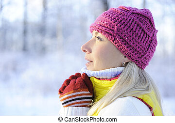 Frozen beautiful woman in winter clothing outdoors