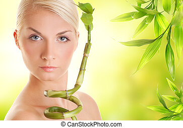 Beautiful young woman with bamboo plant