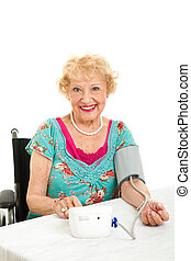 Woman Taking Her Own Blood Pressure - Senior woman taking he...
