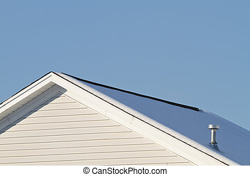 Snow Covered House Roof - A view of a residential houses'...