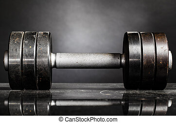 metal barbell on dark gray background