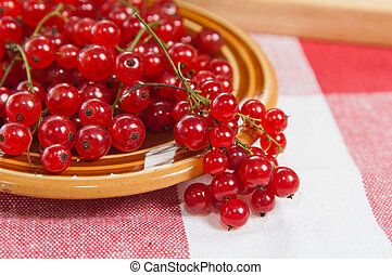 Berries of a red currant in a plate on a table