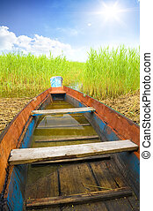 Wooden boat in cane on the bank of lake