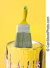 painting supplies - paintbrush on top of yellow paint can...