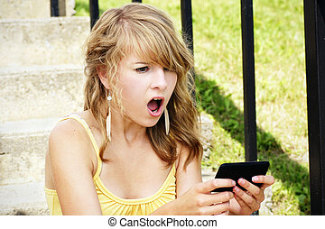 Shocked young blond reading text - Young woman, teenager...