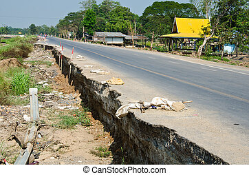 Road crack. - The road has been damaged by flooding.
