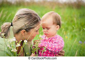 Young mother and her baby girl playing while outdoors on a...