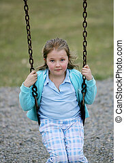 young girl on swingset - smiling female child playing...