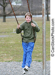 young boy on swingset - smiling male child playing and...