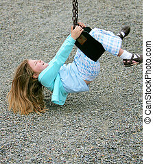 young girl on swingset - smiling female child playing and...