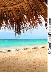 Tropical beach - View from under palm leaves shelter onto...