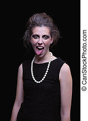 beautiful young woman with elegant black dress, with his tongue out, on black background, studio shot