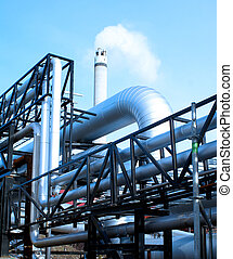 industrial pipelines and smokestack with a natural blue...