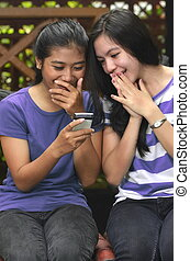 Two Girls sharing a smartphone