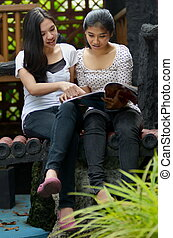 Two Girls Reading magazine together