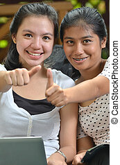 Girls posing thumb with laptop - Two pretty southeast asian...
