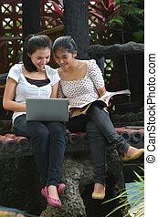 Reading magazine and using laptop