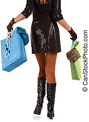 view of woman carrying shopping bag - waist-down view of...