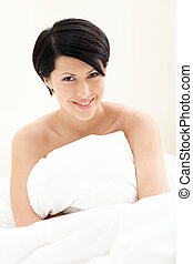 Halfnaked woman hugs the blanket, isolated on white...