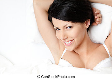 Sleeping woman in the wide bed, white background