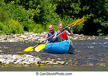 Two people in canoe enjoying holidays and nice weather in...