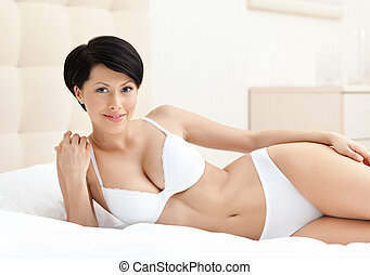 Woman in white underwear is lying in the bed with white...