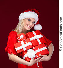 Beautiful lady in Christmas cap hands a set of presents,...