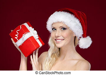 Beautiful woman in Christmas cap hands present, isolated on purple
