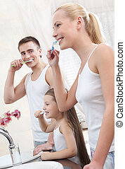 Family of three people brush their teeth - Happy family of...