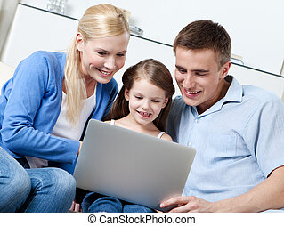 Happy family sit on the sofa with laptop - Happy family of...
