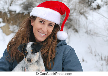 Woman with Puppy - Young woman wearing Santa hat and holding...