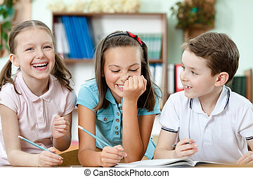Laughing pupils help to each other to do the task