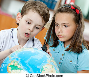 Two pupils look at the globe - Two friends amazingly look at...