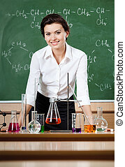 Smiley chemistry teacher is surrounded with chemical glassware with different liquids