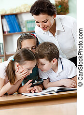 Teacher with her pupils examine something with loupe - Young...