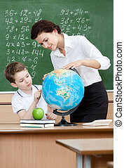 Geography teacher shows something to the pupil at the globe