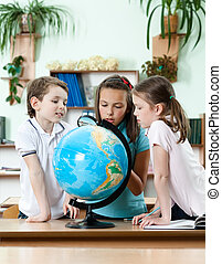 Friends stare at school globe and try to find something with...