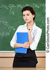 Serious teacher is at the blackboard