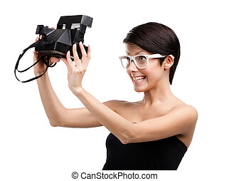 Woman takes images with cassette photographic camera,...