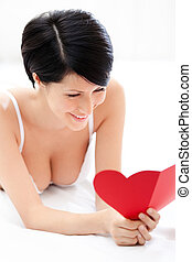 Woman in underwear hands a heart shaped post card while...