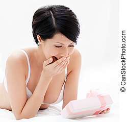 Woman in underwear finds a gift in bed, white background