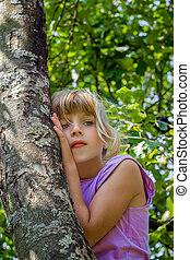 Little girl climbed into a tree and thoughtfully looks...