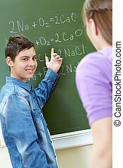 Explaning formula - Clever boy pointing at blackboard while...