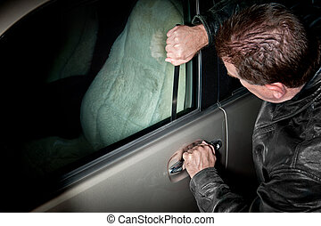 Automobile Thief - A male car thief uses a flat metal lock...