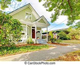 Small cute craftsman American house wth green and white. -...