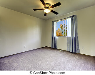 Empty room with curtains, grey carpet  and fan.