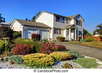 White two story AMerican housee front exterior with large garage.