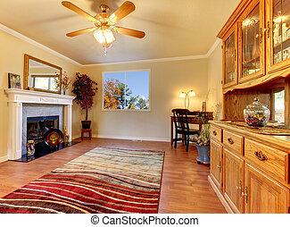 Living room with fireplace and Beige walls with cabinet hutch.